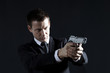 Secret agent aiming with gun against black background