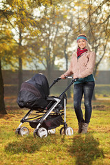 A smiling mother posing with a baby stroller in autumn