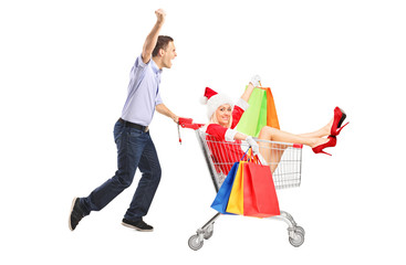 Guy pushing a woman in christmas costume with bags in a cart