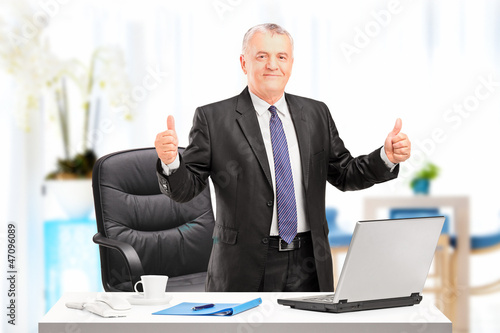 Happy businessman standing in his office and giving thumbs up