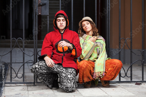 Young hippie couple sitting against an iron fence