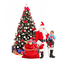 Santa Claus giving a gift to a child in front of christmas tree