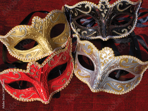 Looking down on some masquerade mask on red background