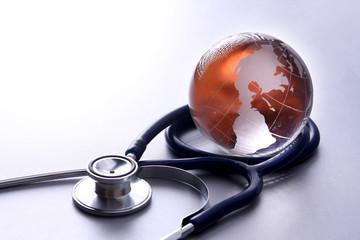 Stethoscope near to glass globe world map