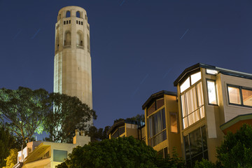 Coit Tower and houses at night in San Francisco, California