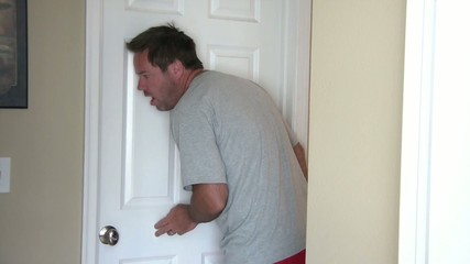 Couple Eavesdropping Against Door
