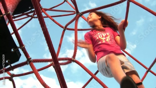 Girl Climbs at Playground in Sun