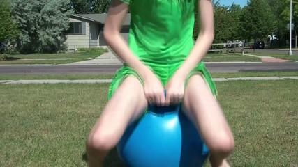 Girl Hops in Ball Past Camera