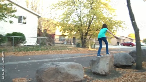 Girl Jumping on Rocks in Fall