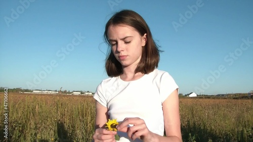 Girl Pulls Petals from Flower Thinking