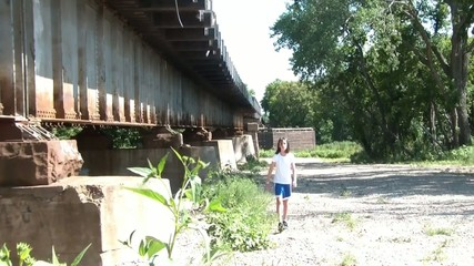 Girl Walking Next to Rusty Railroad Bridge