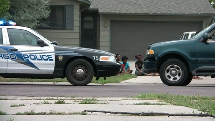 Girls Sit Next to Police Car During Investigation