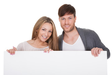 Positive young couple with blank board