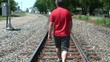 Man Walking Down Railroad Tracks