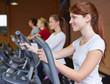 Frau am Crosstrainer im Fitnesscenter