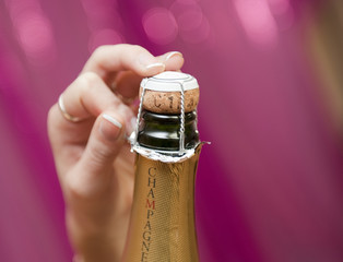 Main ouvrant une bouteille de Champagne