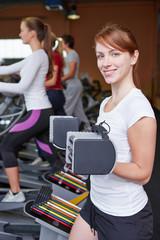 Frau neben Crosstrainer hebt Gewichte