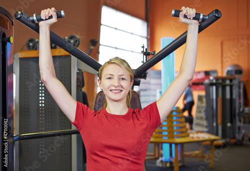 Frau macht Rückenübung an Schulterpresse