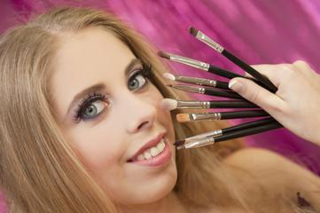 Jeune femme se faisant maquiller pour une soirée