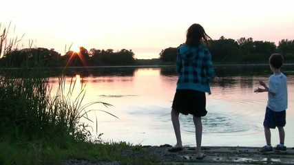 Kids Throw Rocks into Beautiful Lake with Sunset