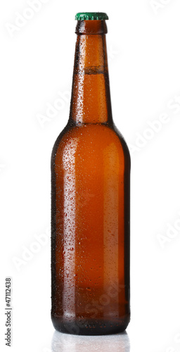 Brown bottle of beer with drops on white