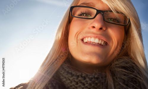 blonde junge frau mit schal und brille lacht