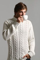 Handsome man in sweater drinking tea