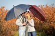 Couple kissing under umbrellas in the park.