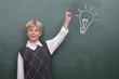 Kind mit Idee vor der Tafel