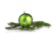 green christmas ball with fir branch isolated on white