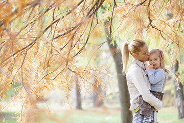 Mother and boy in the autumn forest
