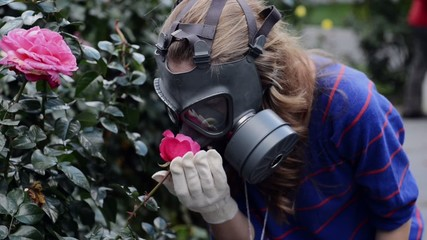 girl in gas masks smells  roses