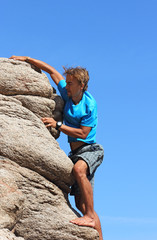 young man climbs on a rock