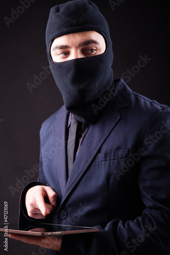 Closeup portrait of a hacker stealing data from digital tablet
