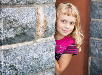 Little girl looks out from behind the wall and smiles
