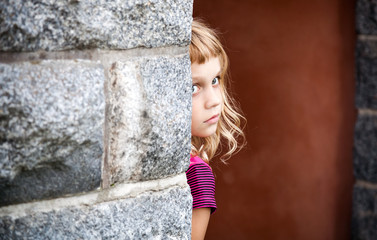 Little blond girl looks out from behind the gray stone wall