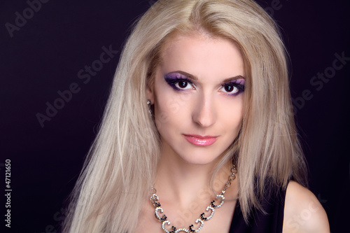 Photo: Portrait of beautiful female model on black background