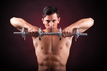 Image of a muscular young man lifting weights on black backgroun