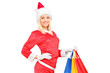A female in christmas costume holding shopping bags