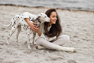 Happy young woman resting at beach in autumn with dog