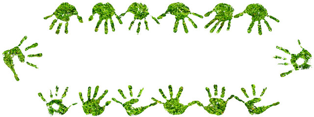 Conceptual human hand prints frame of green grass