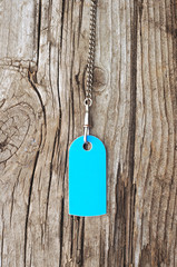 blank blue tag on with silver chain old wooden background
