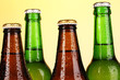 Coloured glass beer bottles on yellow background