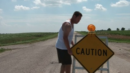 Man Drags Caution Sign into Road