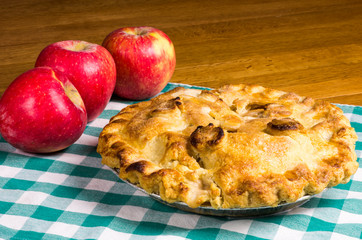 Apple pie and apples on checked cloth