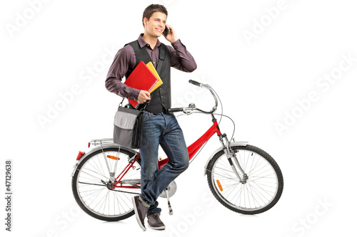 Smiling student holding books and talking on a phone next to a b