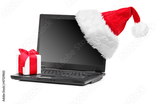 Studio shot of santa hat and gift on a laptop