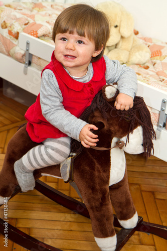 Happy little child and a rocking horse.