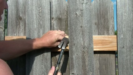 Man Hammering in Nail into Fence