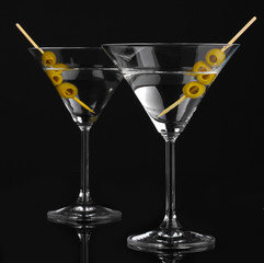 Martini glasses and olives isolated on black